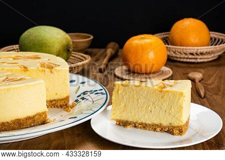 Putting A Portion Of Delicious Homemade Mango Cheesecake In White Ceramic Dish With A Big Loaf Of Ca