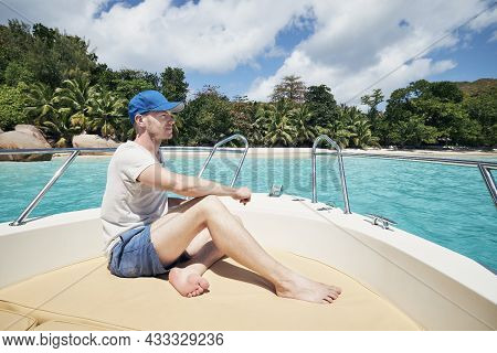 Man Resting On Boat Against Beautiful White Sand Beach With Palm Trees. Anse Lazio, Seychelles.