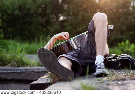 Man Playing A Guitar Laying On His Back Outdoor | Front View Of Man Laying On The Back And Playing T