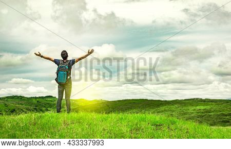 Backpacker Man In The Field Spreading His Hands, Concept Of Successful Man Spreading His Hands