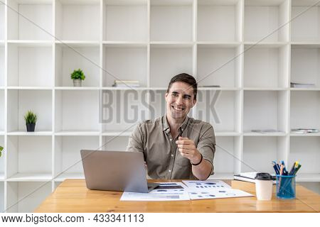 Young Businessman Sitting In The Office Working With Laptop And Paperwork On The Desk, Smiling, He I