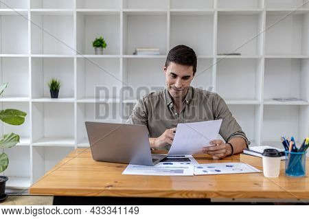 A Young Businessman Sitting In The Office Working With A Laptop, He Is Checking Financial Documents,