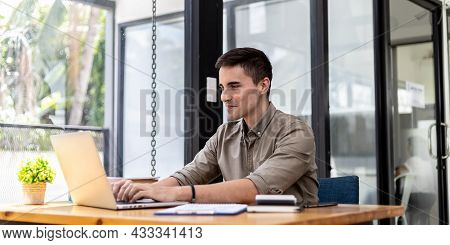 A Businessman Sits In His Office With A Laptop And Stationery, On His Desk There Are Financial Docum