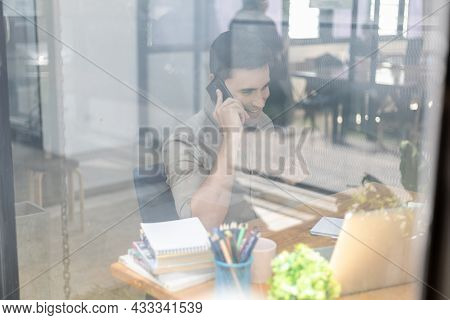 Photo Through The Office Glass Young Businessman Talking On The Phone, He Runs A Startup Company Fou