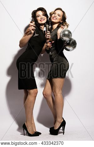 young women in black cocktail dresses sing songs with a microphone and hold glasses of champagne and disco balls