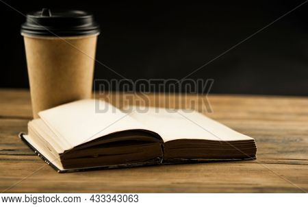 Open book and a cup of coffee in a disposable paper cup on a wooden table