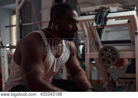 A Man Athlete With Dark Skin Sits In The Gym And Looks Forward. Sport And Healthy Lifestyle Concept.