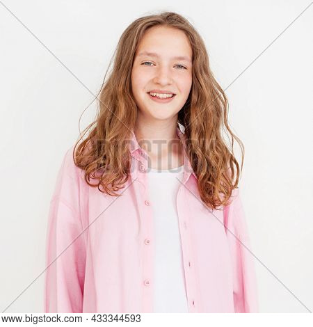Pretty smiling joyfully female with curly hair, dressed casually, looking  at camera, being happy. Studio shot of good-looking beautiful girl isolated against white studio wall Portrait teen student