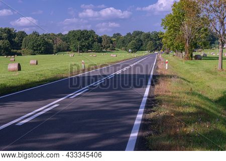 Asphalt Road Through The Plain Covered With Green Meadows. There Are Hay Cuts In The Meadows, There