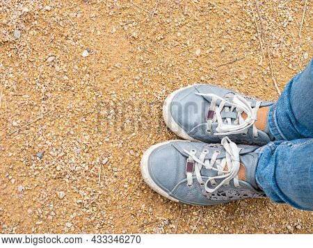 Close-up Of Girl's Legs In Denim Sneakers And Tight Slim Fit Denim Pants. Walk Through The Park On F