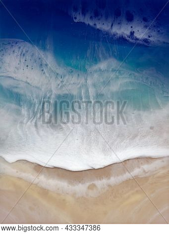 Top View On Sea Wave With White Foam And Light Beige Sand.