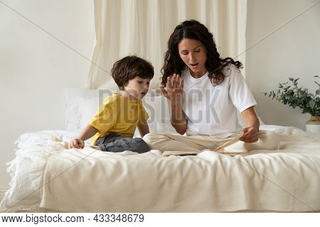 Curly Female Parent Show Images In Book And Read To Cute Little Preschooler Boy. Mother Caring Of Ki