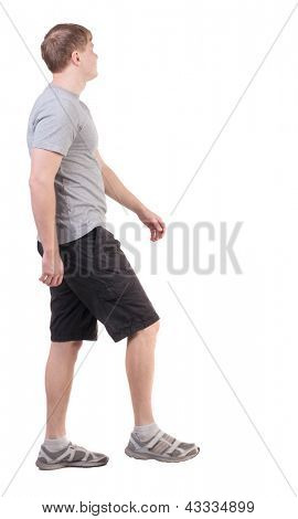 Back view of walking handsome man in shorts and sneakers.   Sports-dressed young man moves. going young guy. Rear view people collection.  backside view of person.  Isolated over white background.