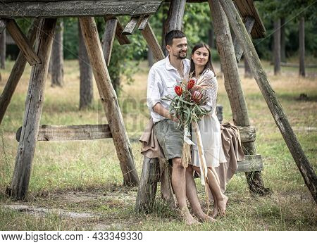 Young Man And Woman Smartly Dressed, With A Bouquet Of Exotic Flowers, On A Date In The Forest.