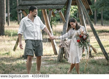 Young Man And Woman Smartly Dressed, With A Bouquet Of Exotic Flowers Are Walking In The Woods, On A