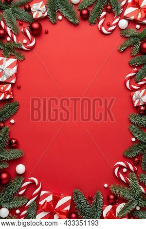 Red background with Christmas gift boxes and Christmas decorations frame. Flat lay, top view and copy space for text