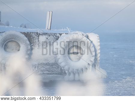 Ice Covered Boat Docks With Tractor Tires By The Baltic Sea In Helsinki, Finland.