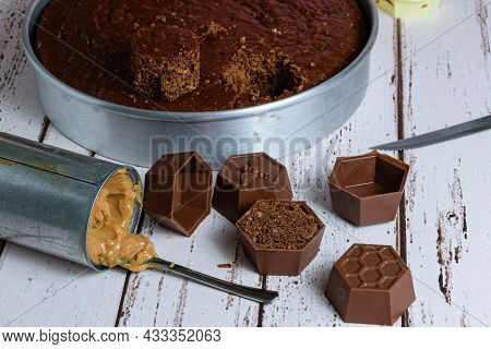 Small Brazilian Honey Cake, Next To A Can Of Dulce De Leche And Small Forms Of Chocolate. In The Bac