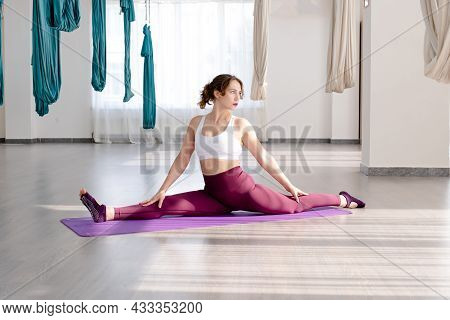 A Young Woman Sits On A Twine. The Woman Performs Stretching Exercises On The Fitness Mat.