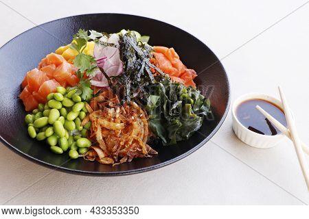 Japanese Poke Bowl With Edamame, Salmon, Wakame Seaweed, Mango, Radish, Cucumber, Onion And Rice Ser