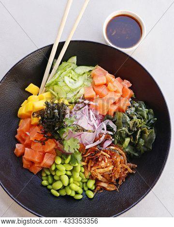 Poke Bowl With Edamame, Salmon, Wakame Seaweed, Mango, Radish, Cucumber, Onion And Rice Served With