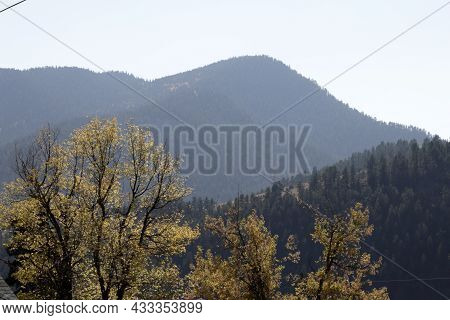 Idaho Springs, Co, Usa - October 7, 2020: Smoky Day View Of Aspen Trees And Evergreen Hills And Moun