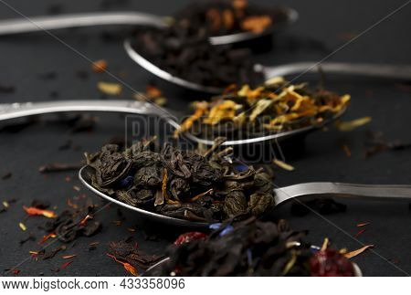 Virious Kinds Of Tea In Tea Spoons On Black Table Close-up, Assortment Of Teas. Black , Green And Fr