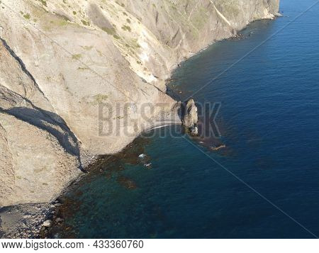 Aerial View From Above On Azure Sea And Volcanic Rocky Shores. Small Waves On Water Surface In Motio