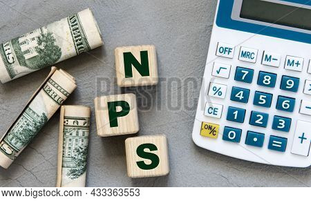Nps (net Promoter Score) - Acronym On Wooden Cubes On A Gray Background With A Calculator And Bankno