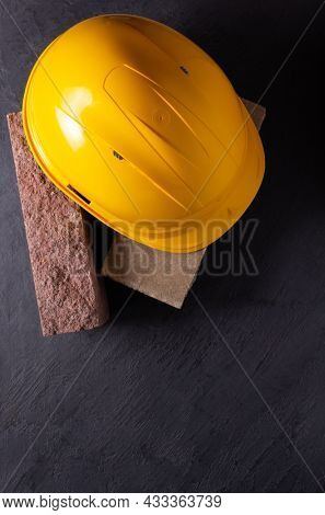 Construction hardhat at brick on black slate stone background. Helmet and bricks