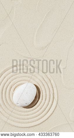 Background With Zen Stone On Sand. Zen Garden With Concentric Circles Around Pebble For Meditation A