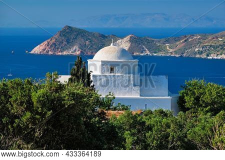 Scenic view Greek Orthodox traditional whitewashed church on Milos island with Aegean sea in background. Milos island, Greece