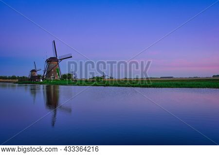 Netherlands rural lanscape with windmills at famous tourist site Kinderdijk in Holland in twilight