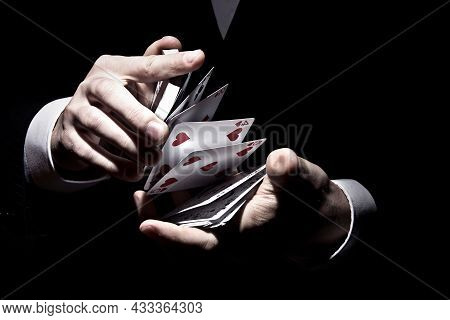 A Magician Shuffling The Cards In A Cool Way Under The Spotlight