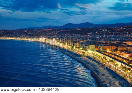 Scenic view of Nice, France in evening blue hour. Mediterranean Sea waves surging on coast, people relaxing on beach, lights illumination on colorful houses