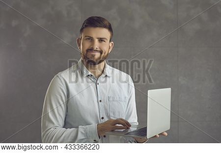 Confident Smiling Business Expert Man Holding Laptop Standing On Studio Wall