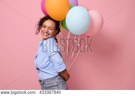 Attractive Stunning Woman In Blue Shirt Smiling With Toothy Smile Looking At The Camera, Holding Mul