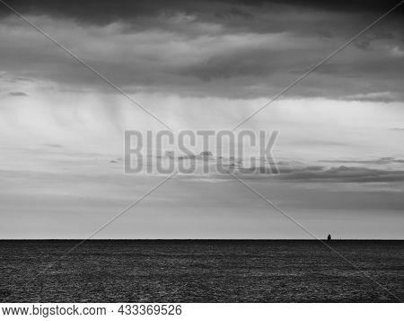 Adriatic Sea Ocean Horizon With Cargo Ship Silhouette In Grado, Italy In Monochrome Black And White