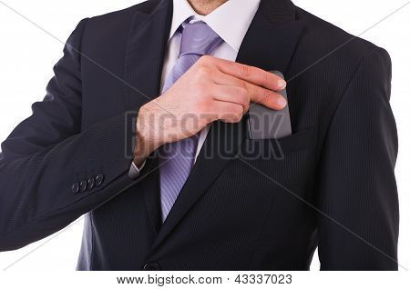 Business man putting cellphone into pocket.