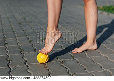 Close-up Of Graceful Bare Feet Of Young Woman Standing On Tiptoes On Spiked Massage Ball On Paving S