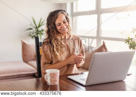 Happy casual beautiful woman working on a laptop at home. Female in headphones have video chat Smiling girl blogger learning webinar