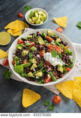 Beef Taco Salad With Romaine Lettuce, Avocado, Tomato Salsa, Black Bean And Tortilla Chips. Mexican