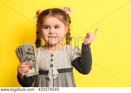 Caucasian Girl Holding Money, Portrait Of A Child On A Yellow Background, Financial Literacy Of Chil