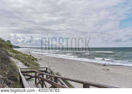 Beautiful Seascape With Waves, Sandy Beach, Old Breakwaters, Cloudy Sky And Wooden Stairs In Foregro