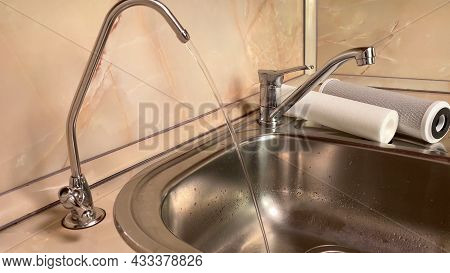 Pouring Filtered Water From Water Filter. Closeup Of Sink And Faucet. Drinkable Water In Kitchen