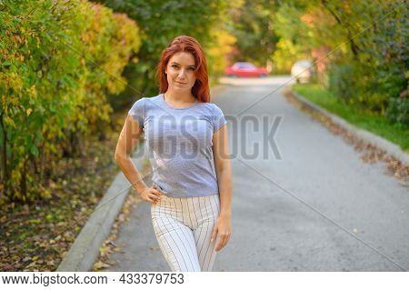 Beautiful Red-haired Woman Posing Outdoors In Autumn.