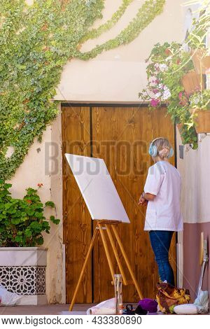 Unrecognizable Artist Woman Painting On Canvas In An Alley Outdoors. Concept Painting Outdoors, Arti