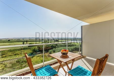 Balcony Terrace, Overlooking The Lake And Park, With Chairs And A Table And Fruit For Picnic And Res