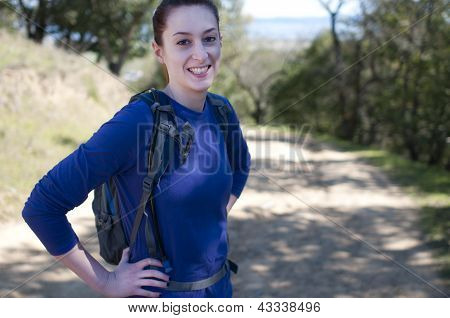 Hiker woman in blue long sleeve shirt looks at camera