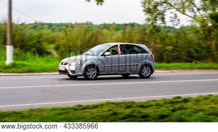 Moscow, Russia - August 2021: Side View Kia Rio Car Second Generation Moving On Rural Asphalt Road.